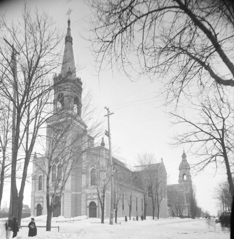 Black and white photograph of a church in winter. A house, trees and four people are part of the landscape. Part of the photograph is hidden, because of the camera lens.