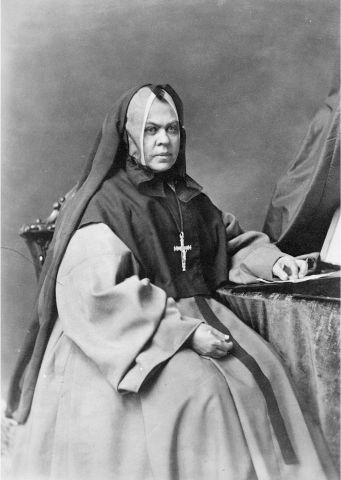 Black and white photograph of a mature nun wearing a black veil and a cross. She is sitting on a chair with a table to her left. Her expression is serious.