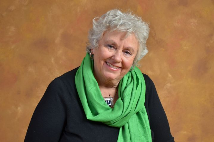 Colour studio photograph of an older woman with curly gray hair. She wears a black jacket, with a green scarf tied around her neck. She is smiling.