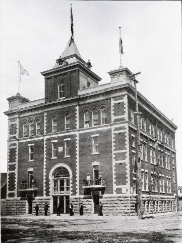 Photographie en noir et blanc d'un édifice en brique de quatre étages. La porte d'entrée est surmontée d'une tour, et deux tourelles sont placées de chaque côté à l'avant de l'édifice. Des drapeaux y flottent.  Des hommes circulent devant l'édifice et on peut voir quelques personnes sur les balcons du premier étage.