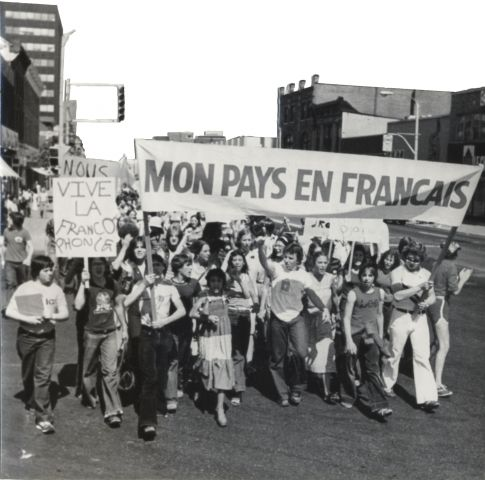 "Black and white photograph of a group of young people protesting in the street. Individual at the front carry a banner reading ""Mon pays en français"" and a placard reading ""Vive la francophonie""."