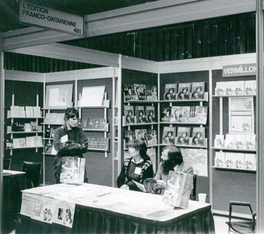 Black and white photograph of a middle-aged man and woman sitting at a table in front of a book display, featuring the magazine Liaison. Standing next to them, a younger woman.