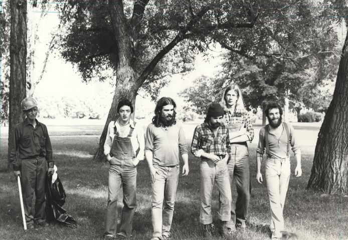 Black and white photograph of a group of five young men in a wooded park. Three have beards, and two have long hair. They wear casual clothing – suspenders, overalls, chequered shirts – and they are walking toward the camera. Next to them, an older man picks up garbage.