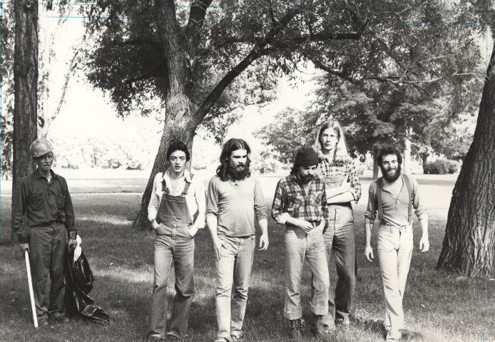 Photographie en noir et blanc d'un groupe de cinq hommes d'âge moyen, dans un parc boisé. Trois portent la barbe, deux ont les cheveux longs. Ils marchent vers la caméra, dans des vêtements décontractés. À côté d'eux, un homme d'âge mûr ramasse des ordures.
