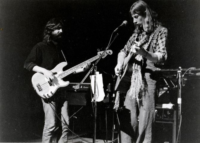 Black and white photograph of two young men, in long hair and casual clothes, on a stage, with amplifiers and an electric keyboard in the background. One of the musicans plays an electric guitar. The other plays an acoustic guitar and stands in front of a microphone.