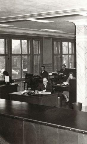 Photographie en noir et blanc de l'intérieur d'un bureau à plan ouvert. Vus de l'avant de la pièce, huit hommes et quatre femmes sont assis à des bureaux, en train de travailler. De larges fenêtres parent un des murs.