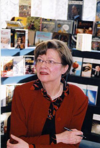 Photographie en couleur d'une femme d'âge mûr, vue de trois quarts. Elle a les cheveux bruns courts et porte des lunettes, un chemisier imprimé rouge et noir et une veste rouge. Elle est assise, les bras croisés sur une table, un stylo à la main droite. À l'arrière-plan, un étalage de livres.