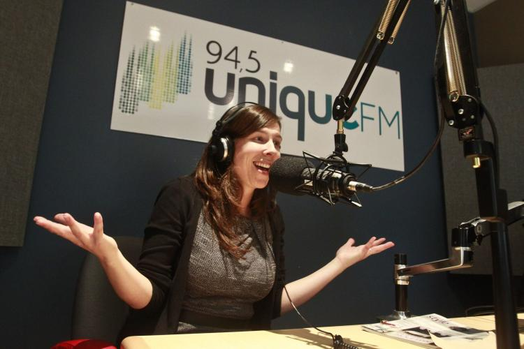 "Colour photograph of a middle-aged, smiling woman in a radio studio. She wears headphones and speaks into a suspended microphone. She sits at a table with her arms raised, hands open, palms up. Behind her, a sign with the words ""94,5 Unique FM."""