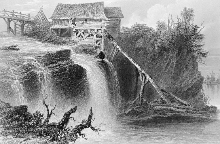 Black and white engraving of a small rudimentary wooden installation located near waterfalls. The mill is located between a wooden bridge and a wooded cliff.