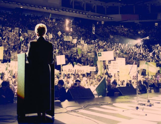 "Colour photograph of a woman seen from behind, standing on a stage, addressing the audience from a podium with a microphone. The stadium is filled with people brandishing signs bearing the slogan ""S.O.S. Montfort."""