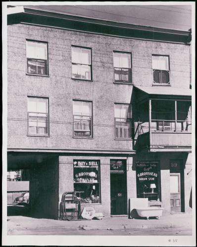 Black and white photograph of a three-storey stucco building with a balcony on the first floor. On the ground floor, a used goods store with bilingual signage at the front. A passageway offers access to the parking lot at the rear of the building.