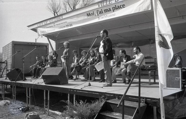 "Black and white photograph of a middle-aged man and woman standing at microphones on an outdoor stage. Behind them, around ten people sitting on benches. Written on a banner above the stage: ""Centre national des Arts–National Arts Centre; Théâtre français saison 83-84; Moi, j'ai ma place; Je m'abonne."""