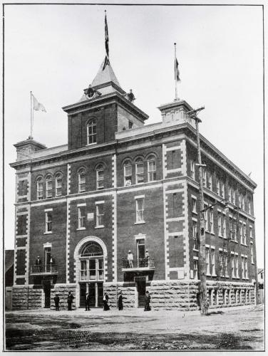 Black and white photograph of a four-storey brick building. The entrance door is topped by a tower, and two turrets are positioned at the front corners of the building. Flags float at the top of the turrets. A few men stand in front of the building; others stand on the first-floor balconies.