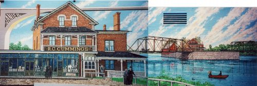 """Color photograph of a mural depicting near and far views of the """"R.C. Cummings"""" commercial building in red brick. The building, located on an island in the center of a river, is reached by a metal bridge."""