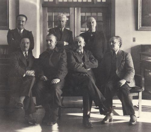 Photographie en noir et blanc montrant sept hommes d'un certain âge dans une salle d'exposition.  Trois hommes sont debout derrière; quatre hommes sont assis sur un banc. Tous sont vêtus de costumes et ont l'air sérieux.