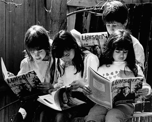 Black and white photograph of four children, each one reading a copy of Liaison magazine, which they hold in their hands. They are outside. Two girls and a boy sit in a row on log stumps, with another boy standing behind them.