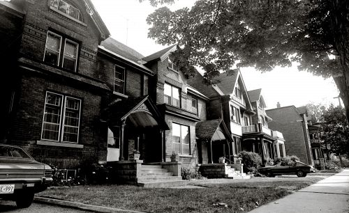 Black and white photograph of several adjoining three-story brick houses with basement, sidewalk views. Cars are parked in two of the driveways. The street is filled with trees, and flowers grow in the small, well-maintained yards.