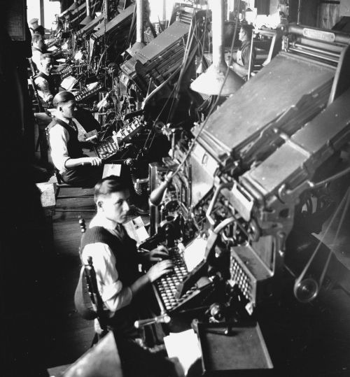 Photographie en noir et blanc de cinq hommes en chemise, gilet et cravate dans un atelier industriel. Ils sont assis devant d'imposantes machines de composition, avec clavier.
