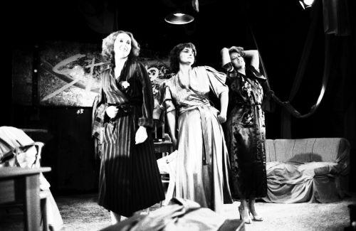 Photographie en noir et blanc de trois femmes d'âge moyen, en peignoirs sur scène. Une des femmes pose une main sur sa hanche. Une autre a les yeux fermés et les mains derrière la tête. La dernière femme porte une serviette sur son bras. Derrière elles, un divan; au mur, une bannière.