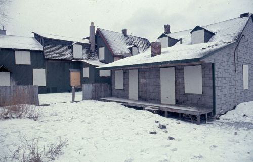 Colour photograph of four houses boarded-up in a winter landscape.