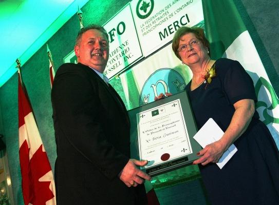 Photographie en couleur, légèrement bleutée, d'un homme d'âge mûr et d'une femme d'un certain âge debout sur une scène, tenant un certificat encadré. Derrière eux, un drapeau franco-ontarien et les logos de divers organismes, verts pour la plupart.