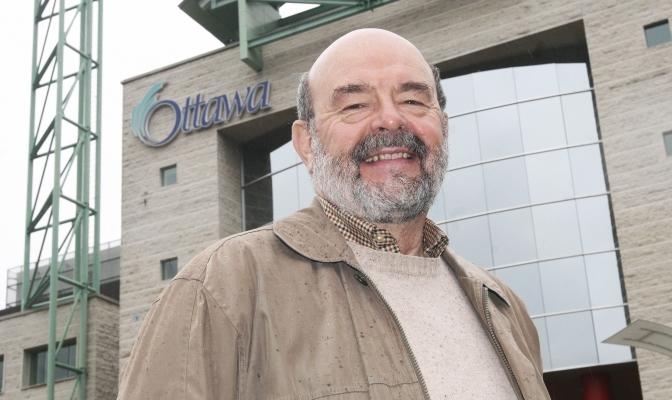 Photographie en couleur d'un homme d'âge mûr, atteint de calvitie et portant une barbe poivre et sel. Il revêt un manteau beige couvert de gouttes de pluie. Il est debout devant un édifice de plusieurs étages fait de blocs de béton gris et de verre, arborant l'enseigne de la Ville d'Ottawa.