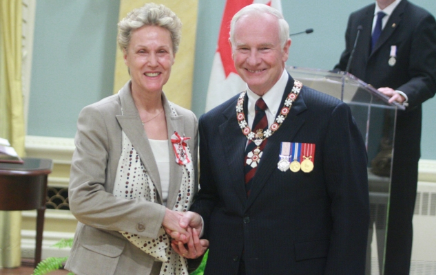 Colour photograph of a mature woman wearing a beige jacket and matching patterned scarf. The Order of Canada badge is pinned to her jacket. The woman is accompanied by an elderly man wearing a suit, tie, medals and the chain of office of the Governor General of Canada. The two decorated people shake hands during a ceremony. The flag of Canada is visible behind them.