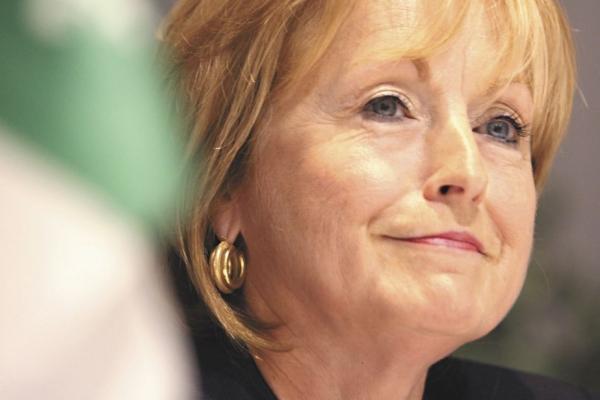 Photographie en couleur d'une femme d'âge mûr aux cheveux blonds, vue de trois quarts en très gros plan.  À l'avant-plan, une partie du drapeau franco-ontarien est hors foyer.