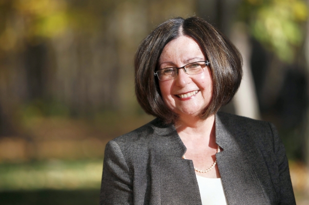 Outdoor colour photograph of a smiling middle-aged woman with glasses and dark hair reaching her chin. She wears a dark gray jacket over a white top, and a pearl necklace. Trees are visible in the background.