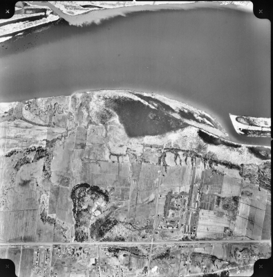Black and white aerial photograph of a rural landscape with a river to the north (at the top of the image). A few dwellings are grouped to the south, along two main roads (at the bottom of the image).