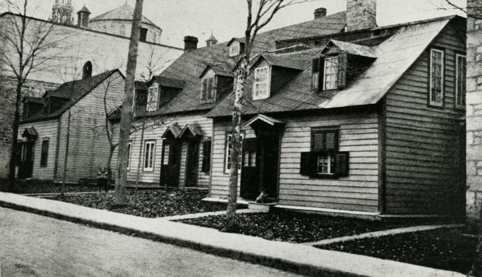 Photographie en noir et blanc de trois petites maisons en bois à deux étages. Les maisons sont très rapprochées les unes des autres, près d'un grand édifice religieux en pierre.