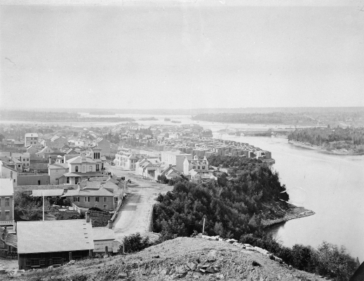 Black and white photograph of an urban landscape, viewed from above. An imposing river borders it to the right, crossed by a bridge that leads to a wooded area. In the distance, reaching far into the distance, the forest.