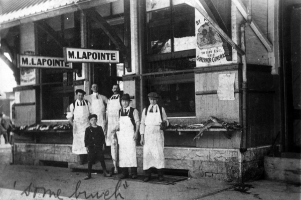 Black and white photograph of a boy and five men in white aprons, standing in front of a fish store. Signs indicate the company's name and its distinction as a supplier to the Governor General.