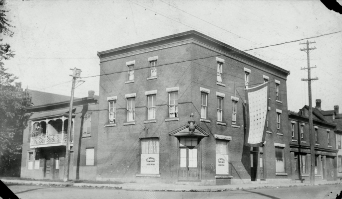 Black and white photograph of a three-storey brick building. Posters in two windows on the ground floor bear the name of the organization. A banner patterned with maple leaves is suspended, flag-like, from the second floor of the building.