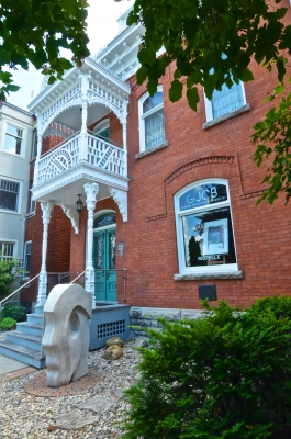 "Colour photograph of a two-storey red brick building. The front is decorated with a white-washed wood balcony. In front of the entrance, a sculpture of a stylized head in profile. In the window, a table and the name of the business, ""GJCB Galerie Jean-Claude Bergeron."""