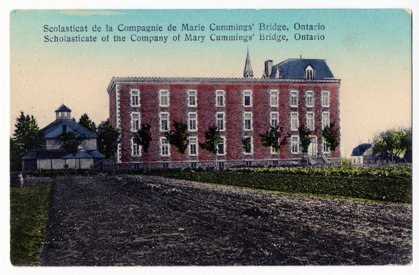 Colour postcard with text printed in French and English. A dirt road leads to a three-storey red brick building topped by a bell tower. Small trees grow alongside the building. On one side of the structure, an outbuilding; on the other side, a small house.