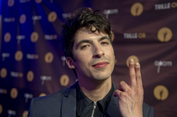 Photographie en couleur d'un jeune homme. Il a les cheveux noirs ébouriffés et porte un veston gris et une chemise noire. Il pointe l'index et le majeur de sa main gauche vers le haut. À l'arrière-plan,  un voile brun avec des cercles dorés et des inscriptions en blanc, sous un éclairage bleu.