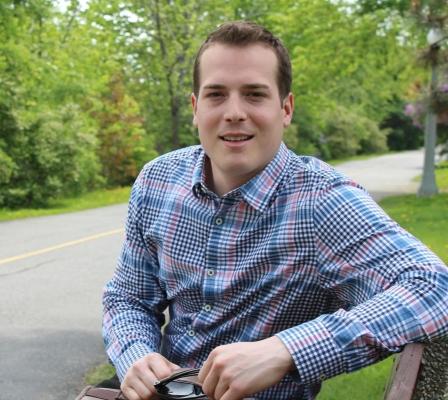 Photographie en couleur d'un jeune homme aux cheveux bruns. Il est assis sur un banc de parc et s'est retourné pour faire face à la caméra. Il a le regard perçant.