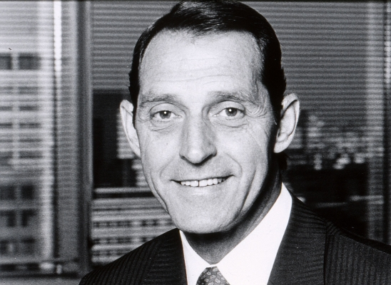 Black and white photograph of a smiling, dark-haired, middle-aged man wearing a suit and tie. He stands in front of a window with a view of high-rise buildings.