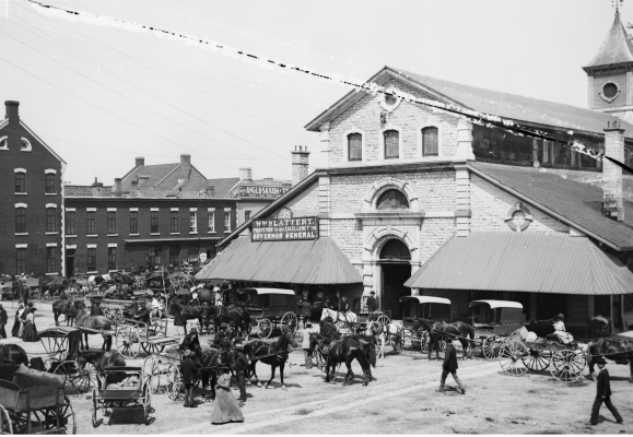 Black and white photograph of a three-storey stone building with awnings. Many people, along with different types of horse-drawn conveyances, wait in the square in front of the building.