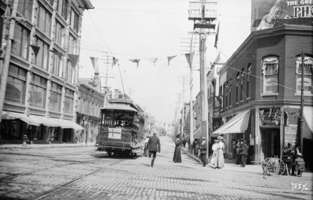 Black and white photograph of a streetcar on a wide commercial boulevard decorated with streamers. People walk on the sidewalks and enter the streetcar.