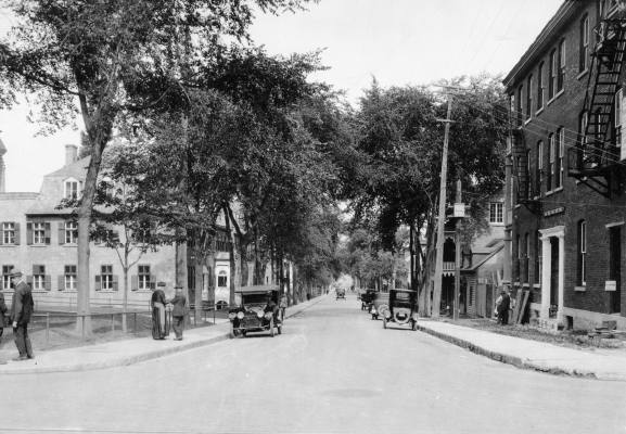 Black and white photograph of a busy street lined with trees, also many cars and pedestrians. Residences line one side of the street, with an institutional building situated on the opposite side. Men,  including a man of the cloth, talk on the sidewalk.