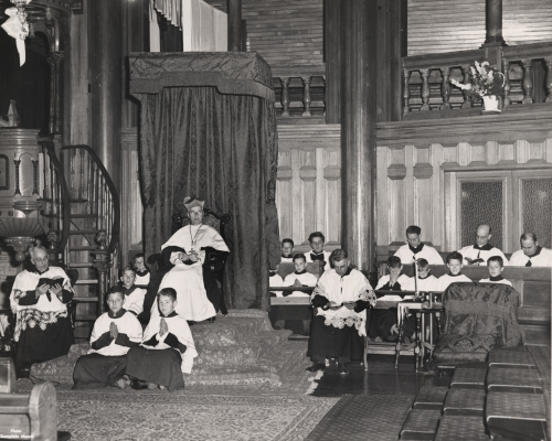 Black and white photograph of a mature cleric wearing the biretta, sitting in a raised chair next to the pulpit. He is surrounded by five other clerics and young altar boys, all dressed in cassocks and surplices.