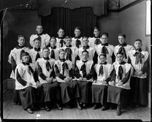 Black and white photograph depicting a group of fifteen boys. Some are sitting, with others standing behind them in two rows. They all wear cassocks and surplices.