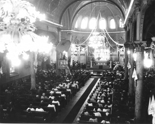 Black and white photograph of the interior of a church seen from above. The church is richly decorated. Attendance is strong.