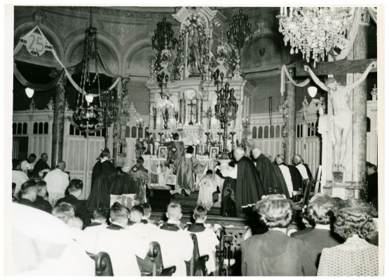 Black and white photograph of clerics praying at the altar of a church. Other clerics and lay people attend the ceremony.