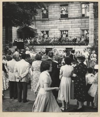 Photographie en noir et blanc d'un attroupement devant un édifice en pierre, aux fenêtres richement décorées. Le groupe inclut des hommes et des femmes ainsi que des religieuses et des enfants.
