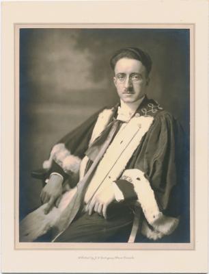 Photographie en noir et blanc, prise dans un studio, d'un jeune homme avec des lunettes et une petite moustache. L'homme est assis et porte une épitoge en fourrure. Le nom du photographe et l'adresse de son studio sont imprimés, en anglais, en bas de la photographie.
