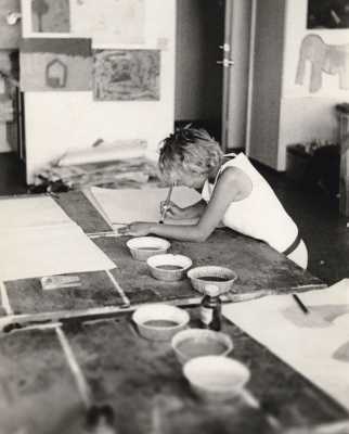 Black and white photograph of a grl in an art studio. She is painting, leaning on a table covered with large sheets of paper and small containers of paint.