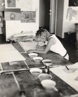 Photographie en noir et blanc d'une jeune femme dans un studio d'art. Elle est penchée sur une table recouverte de grandes feuilles de papier et de petits récipients de peinture, en train de peindre.